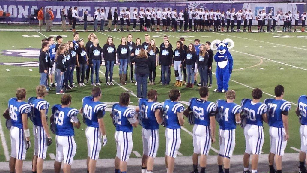 The Cotter football team lines the side of the field as the show choir sings the national anthem in 2019