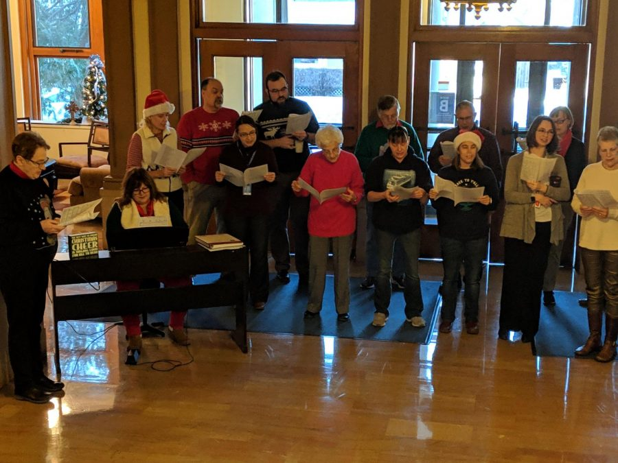 Current+and+former+Cotter+faculty+and+staff+sing+Christmas+carols+in+the+foyer+on+Monday.+