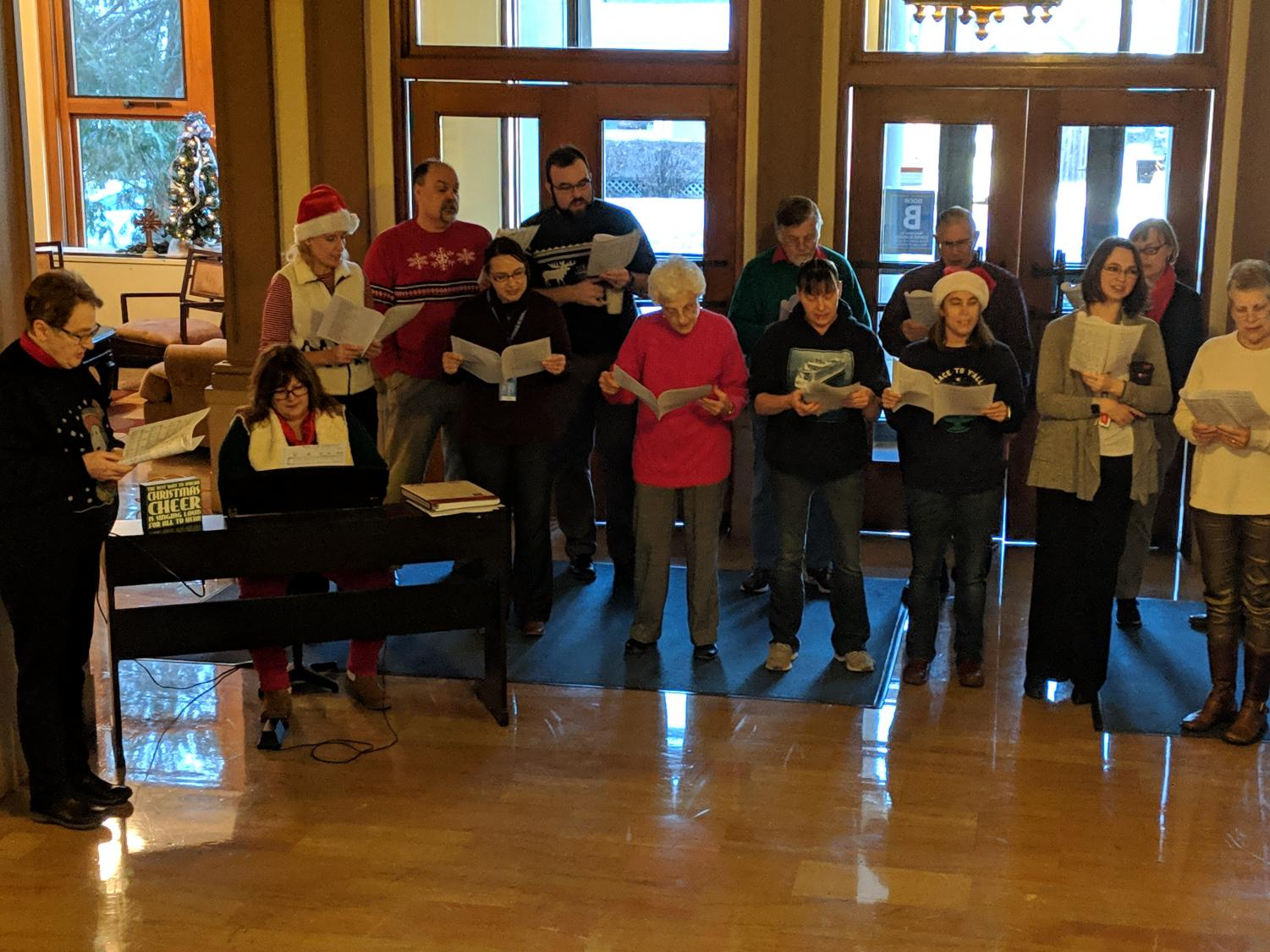 Current and former Cotter faculty and staff sing Christmas carols in the foyer on Monday.