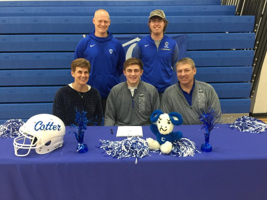 Laken Macal poses with parents and coaches as he commits to play football at UW-Stout
