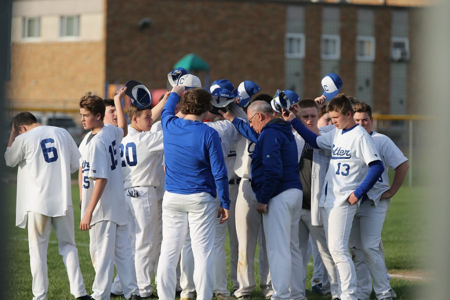 The Cotter baseball teams huddles together at the end of a game.