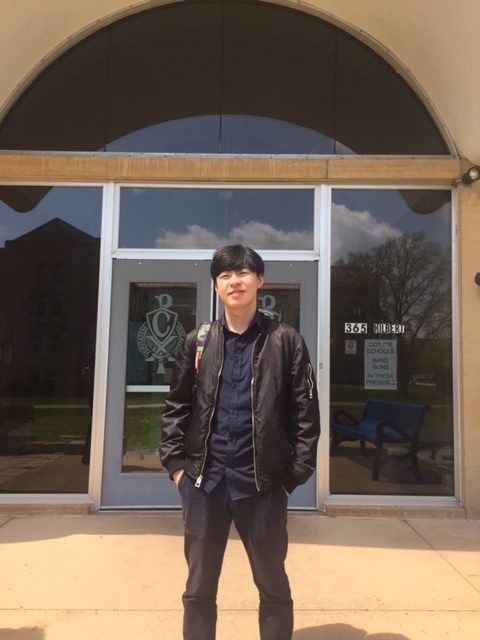 Scott Zhu stands in from of the Loretto Hall dormitory where he spends on time online matching buyers and sellers of custom and rare sneaker