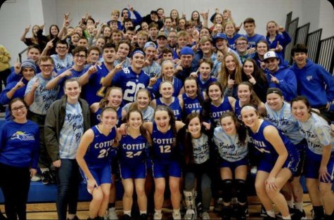 Cotter girls varsity basketball team celebrates with student section after a big win against Stewartville.