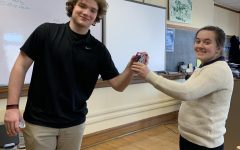 Charlie Reilly delivers a can of Crush to Fiona Flanagan as part of the National Honor Society's fundraiser.