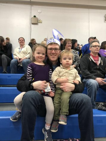 Pictured L to R: Willow Reigstad, Tom Reigstad, and Cedar Reigstad enjoy the Cotter girls basketball game during Catholic Schools Week.