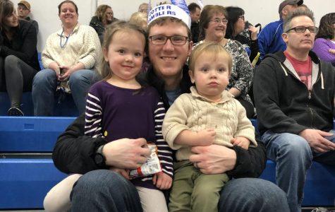 Pictured L to R: Willow Reigstad, Tom Reigstad, and Cedar Reigstad enjoy the Cotter girls basketball game during Catholic Schools Week.