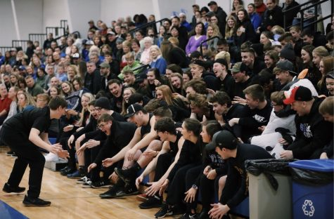 "8th grader Brett Biesanz leads the student section in ""the Rollercoaster""  cheer during a recent girls varsity game"