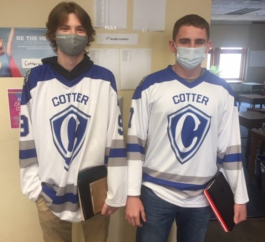 Noah Lange and Ashur Rouleau in their Cotter hockey jerseys