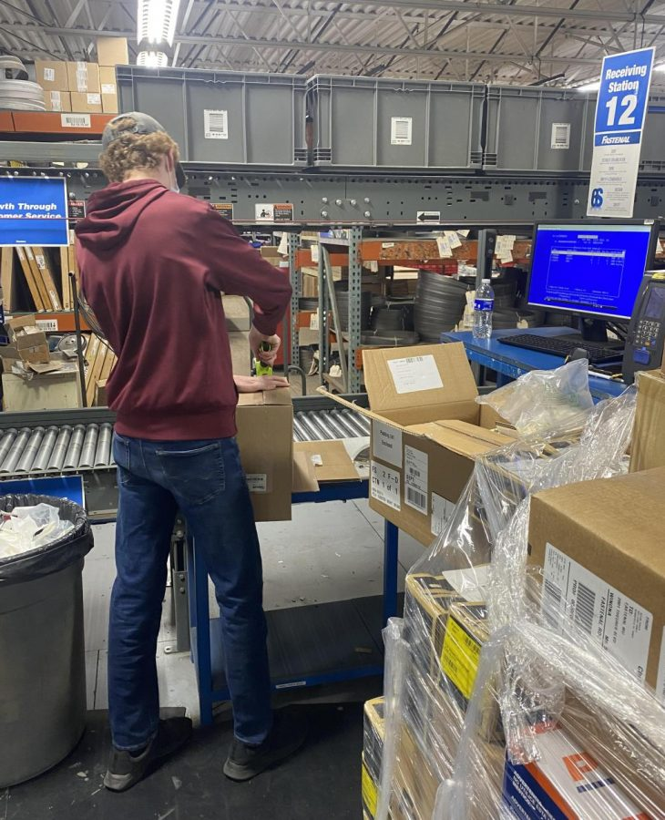 Braden wrapping packages in the receiving department at Fastenal