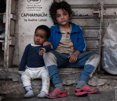 A scene in Capernaum, Zain and Yonus sit beside the street