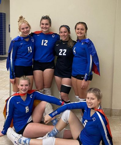 Cotter senior volleyball players pose in capes after their victory on senior night: Top row: Madison Remarkiewicz, Olivia Blumers, Ali French and Andie Teske,  Seated: Rachel Millering and Lexi Danielson
