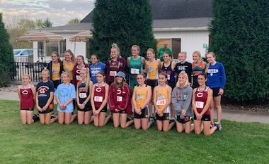 The 21 girls who earned all-conference honors in cross country gather for a photo after the race